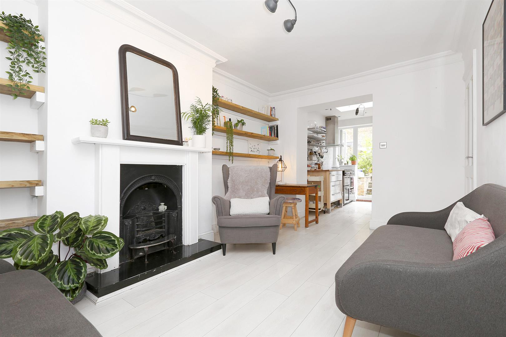 A photo of a open plan living room with a cast iron fire place and indoor plant.