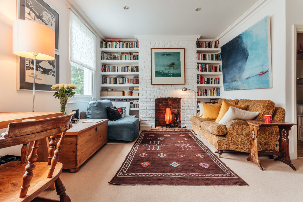 The interior of a living room in a property in stroud green, with a fireplace and a bookshelf