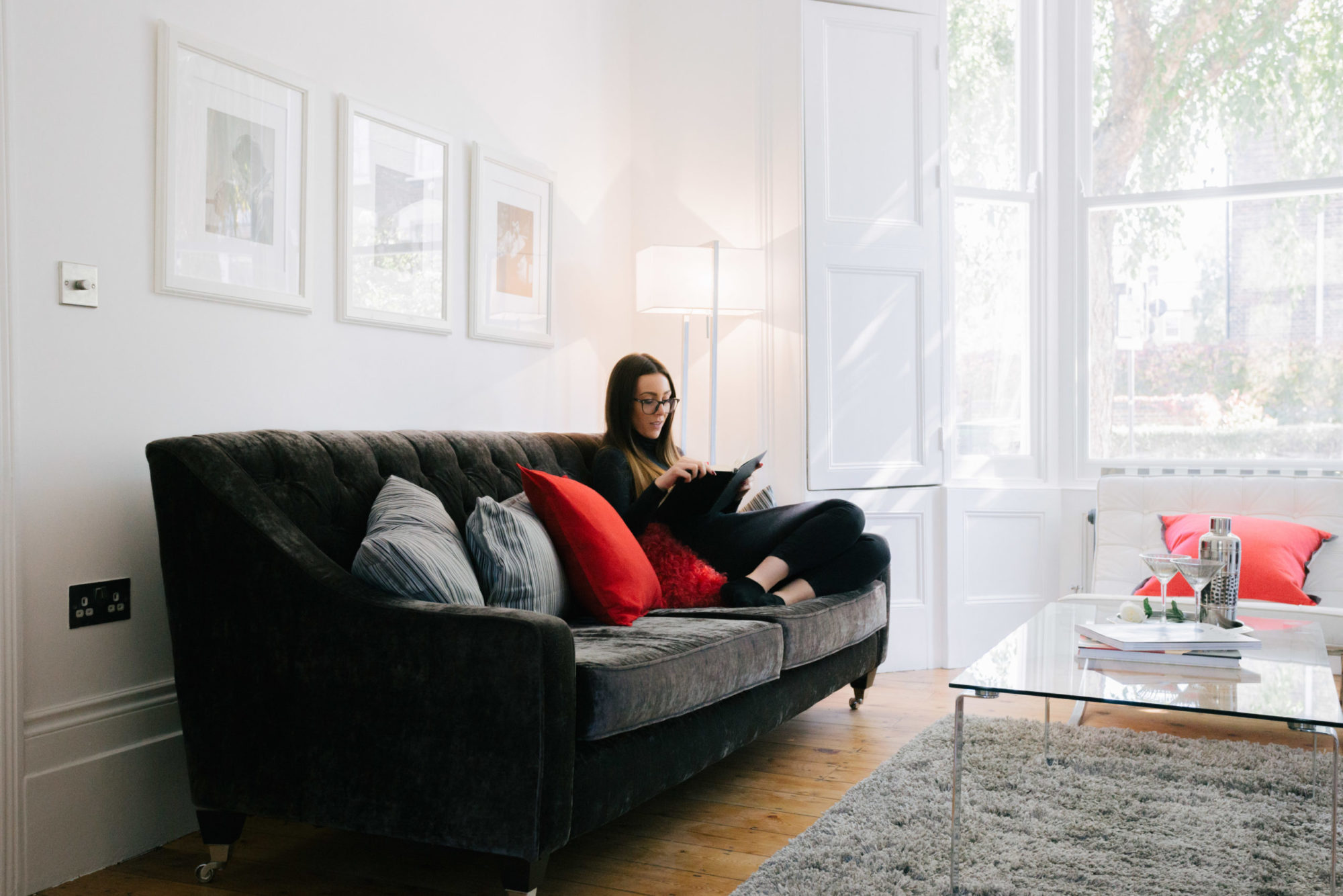Photo of a woman sat on a sofa reading.
