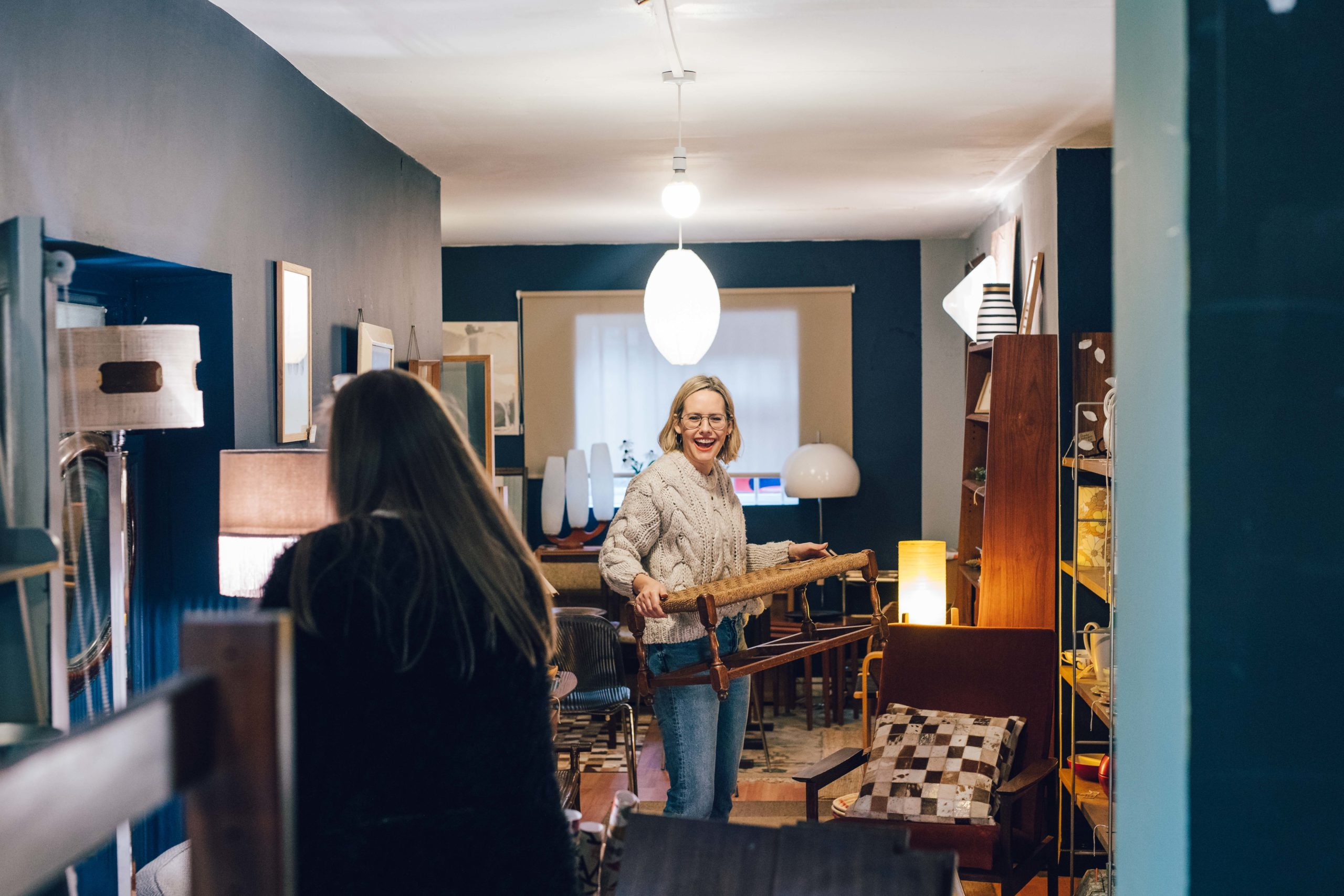 Women moving around furniture and laughing