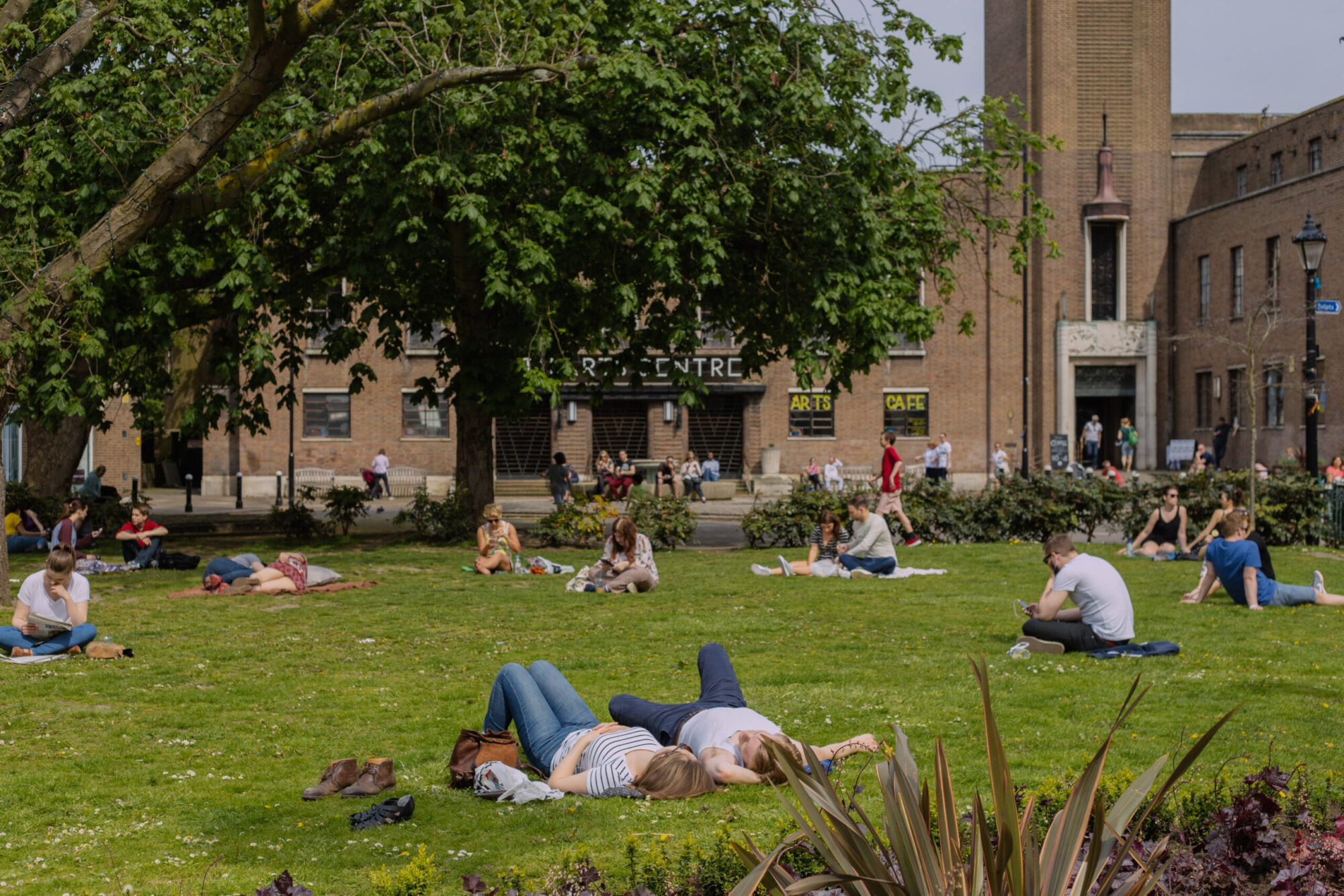 People sitting and lying on the grass of a local park in Crouch End.