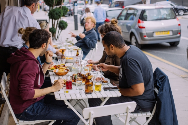 People eating in the outdoor area of a local restaurants in Harringay
