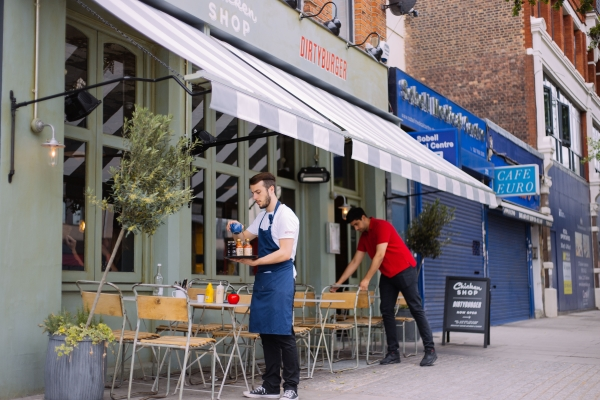A waiter clearing the outside tables of a restaurant in Holloway.