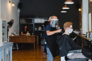 A picture of Em cutting a customer's hair with social distance regulations as he wears a mask and face visor.