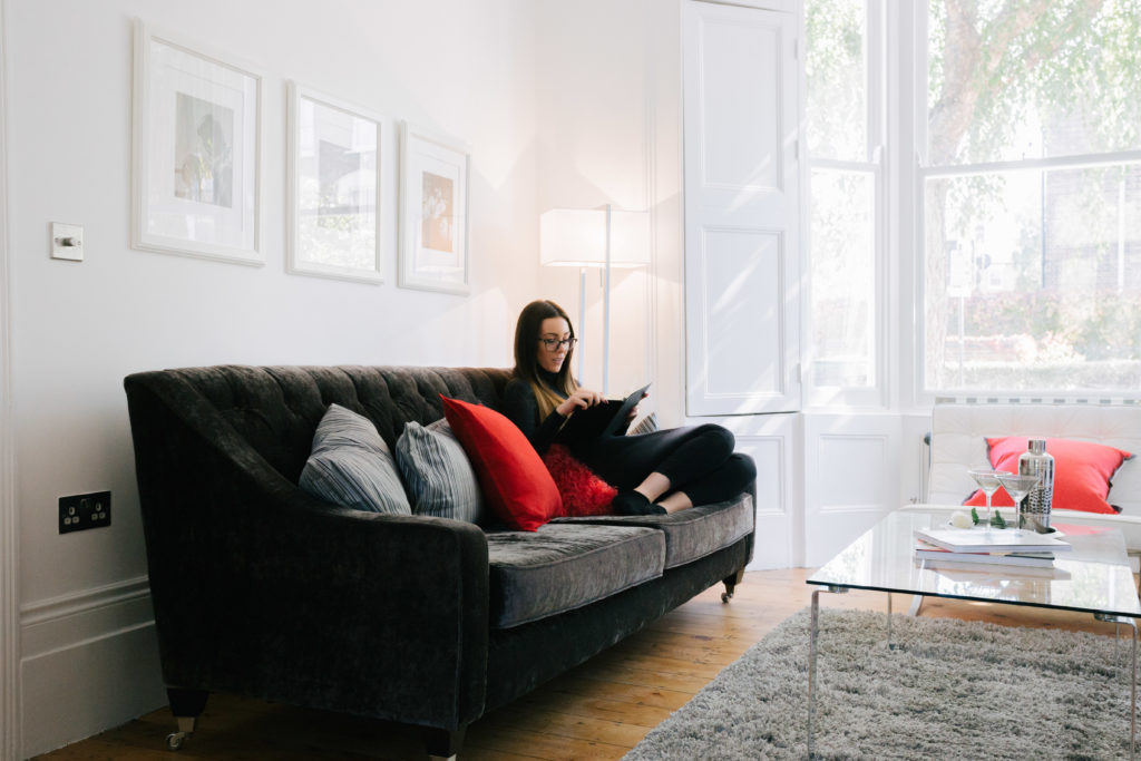 A tenant sitting on the sofa in their home.