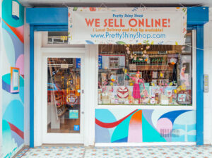 """The outside of Pretty Shiny Shop with a banner saying """"We Sell Online"""""""