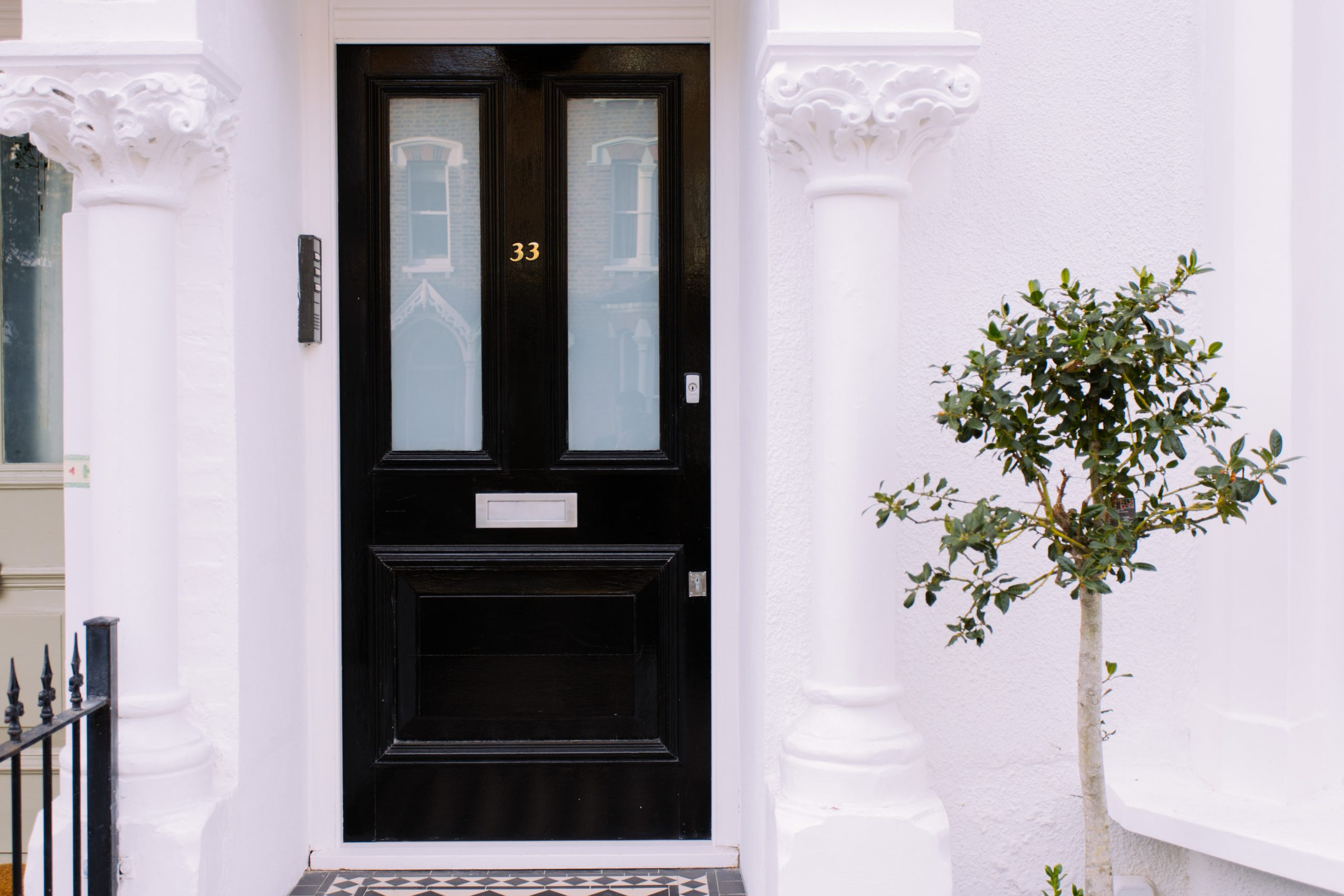 A picture of the front of a property with a gloss black front door, two white pillars either side of the porch and a small tree.