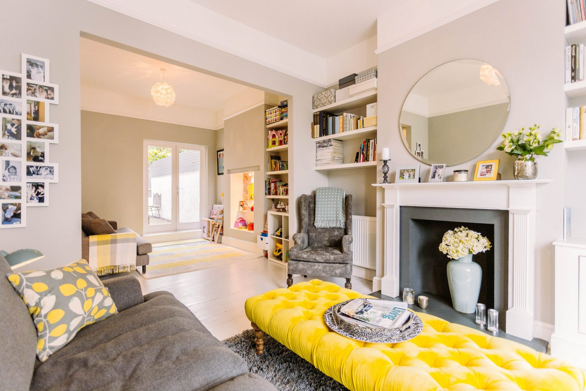 A picture of very cosy looking open plan living room with a bright yellow padded table