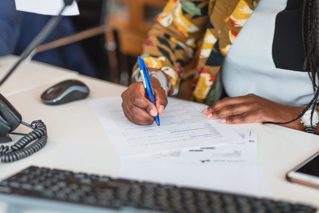 Photo of a member of Davies & Davies filling out a tenant referencing form with a prospective renter.
