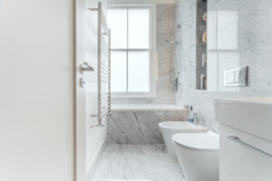 A photo of an immaculately presented modern bathroom with a marble finish floor to ceiling tiles